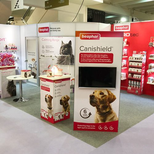 Beaphar Exhibition Stand, Tension Fabric, Red and White Stand with large amounts of product display and shelving and TV displays and a semi-private seating area.