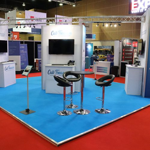 Cab Treasure Blue and White Exhibition Stand, on a raised platform floor, with lighting gantry, tension fabric towers and a small storage room.