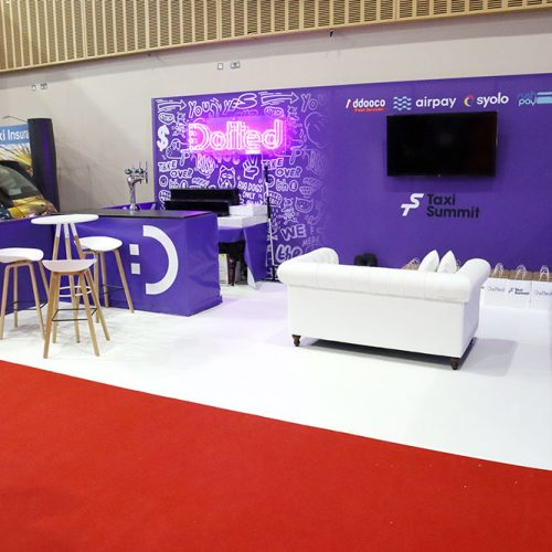 Dotted purple Exhibition Stand, a 5.5M back wall featuring a neon light and large flat screen TV for demo, stand features a bar area and dwarf walling to the sides