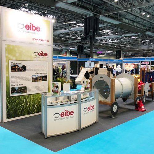 Eibe Island Exhibition Stand, with a simple store room tower with large graphics, and a large reception desk incorporating product display