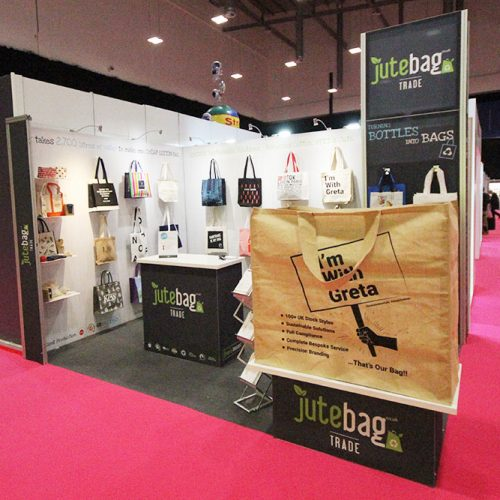 Jutebag Grey and White Exhibition Stand, utilising magnetic hooks for displaying products on tension fabric walls, a small reception desk and a large feature jute bag on the front corner of the stand space