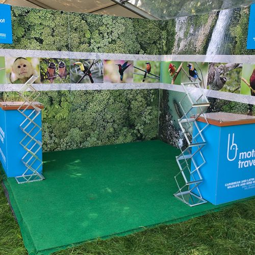 Motmot Travel outdoor Exhibition Stand, built within a large marquee the stand was built on a raised platform floor, and had large tension fabric walls and two small reception desks, and literature stands