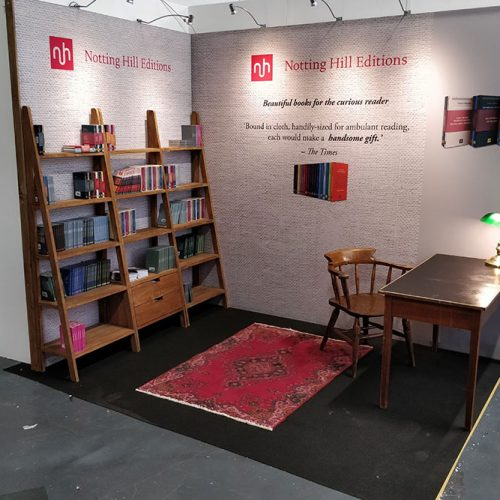 Notting Hill Editions Exhibition Stand featured large fabric graphics, with shelving units from an online retailer, and vintage desk, lamp, chair and rug to give the effect of a writers desk