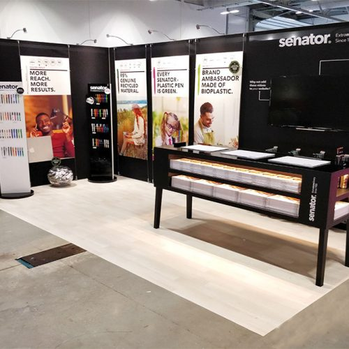 Senator Pens Tension Fabric Exhibition Stand utilised simple black graphics with foamex graphics attached to the stand with a wire system, free standing product displays and a large reception desk